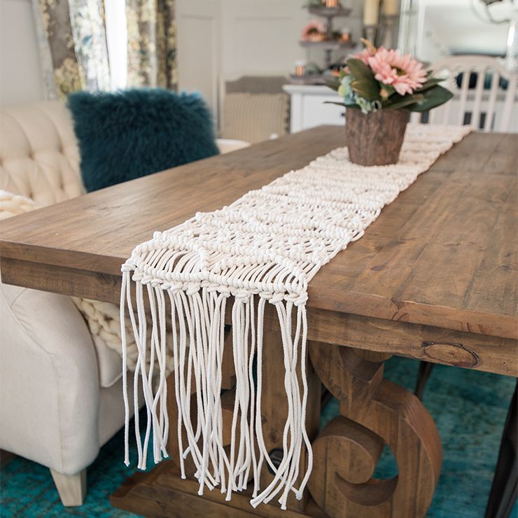A macrame table runner on a dining room table