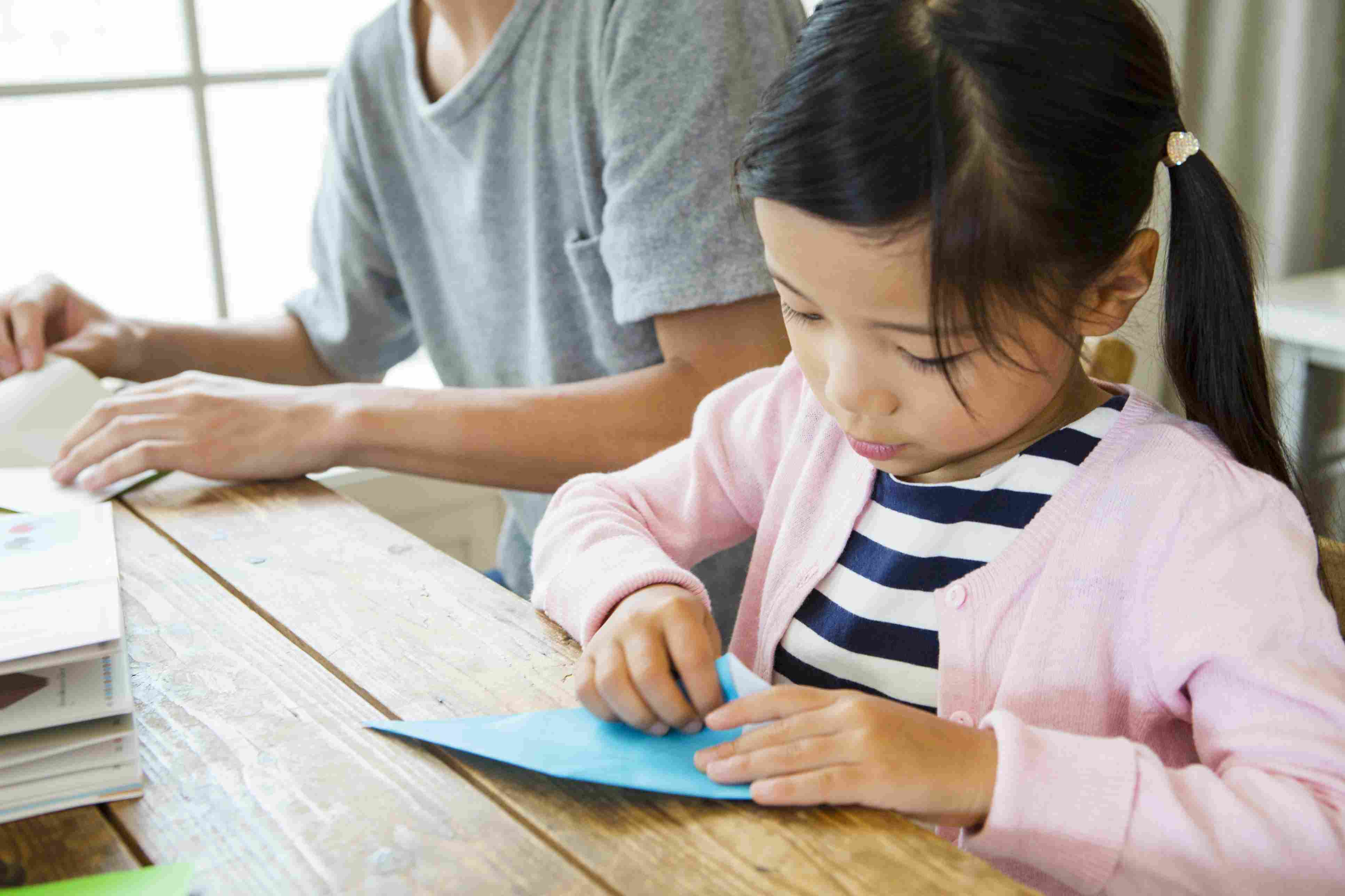Girl folding origami next to father
