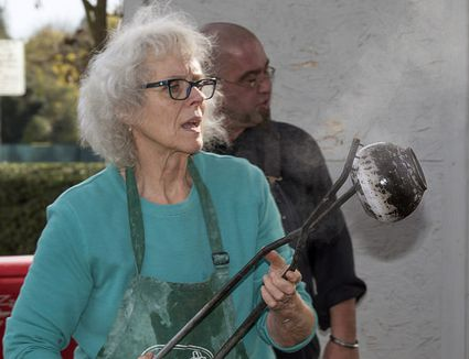 Mary Cargile working her Obvara pots during Raku pottery firing at El Camino Fundamental High School, Sacramento, Calif., Nov. 6, 2014.
