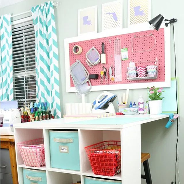 A white craft table with a pink pegboard
