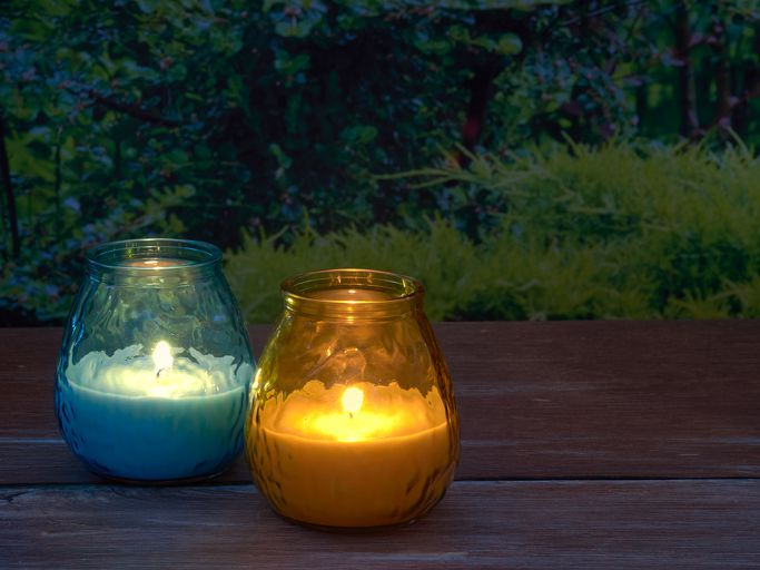 Lit citronella candles in colored jars
