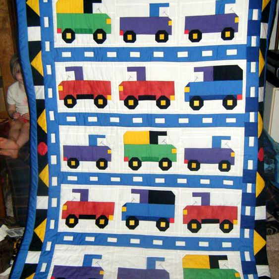 Baby quilt with trucks and cars.