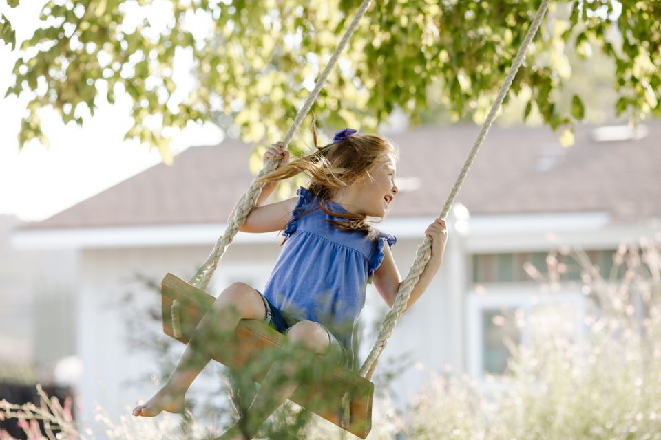 Happy girl swinging on rope swing at front yard