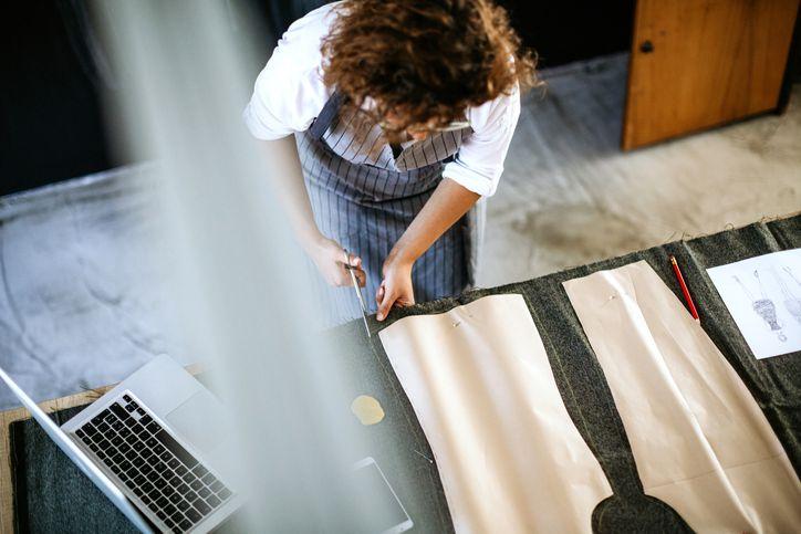 Seamstress cutting fabric around pattern