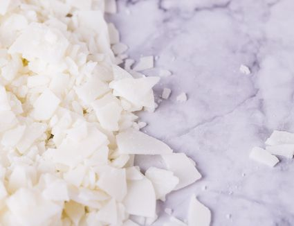 White soy wax flakes for candle making on a gray marble background