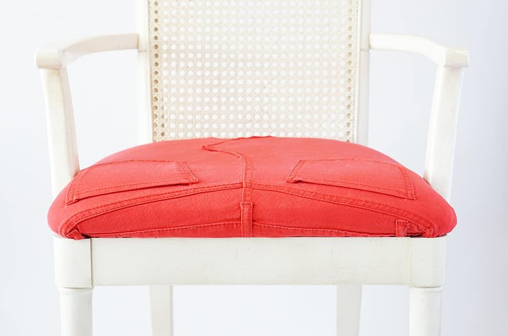 A chair with an orange denim seat