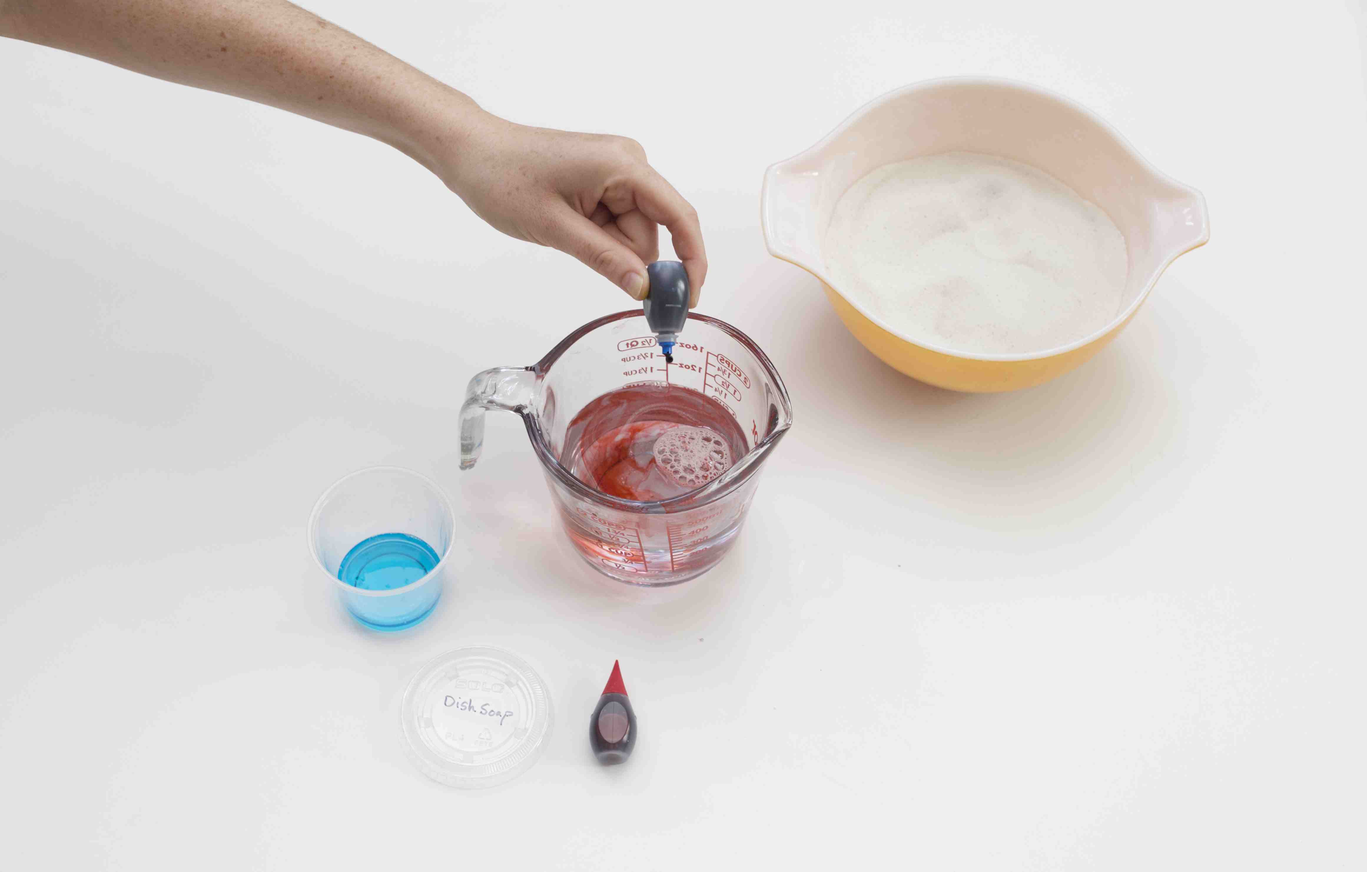 Adding food coloring to dish soap and water solution
