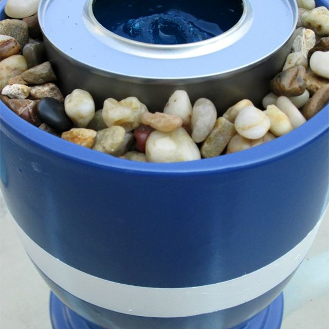 A small blue and white fire pit on a patio table