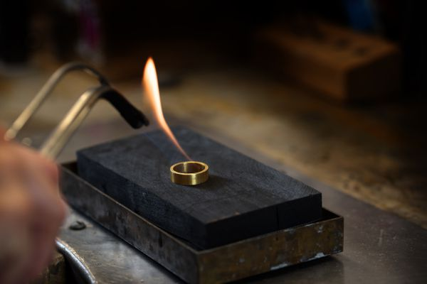 golden ring is annealed with a gas flame in a jewelry factory, copy space in the dark background, selected focus, narrow depth of field