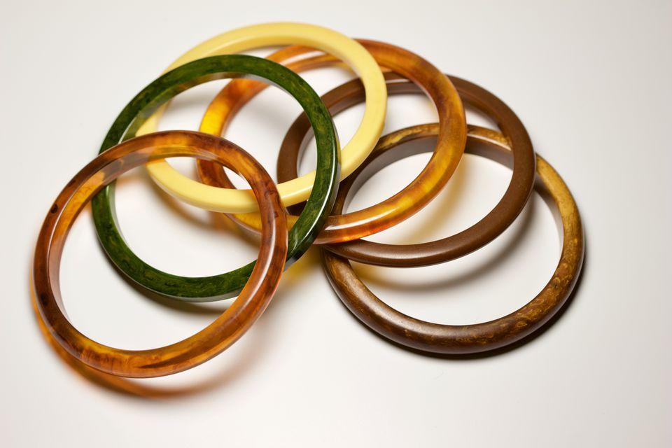 Close-up view of multi-color vintage bakelite bangle bracelets on a white background