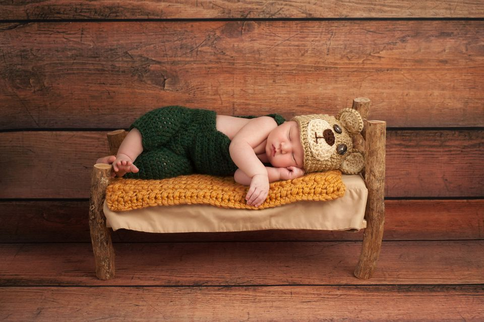 Baby in Crochet Hat and Overalls on Blanket