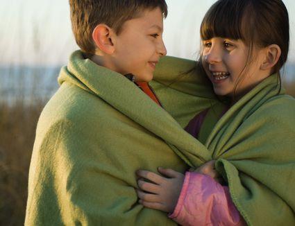 children wrapped in a fleece blanket