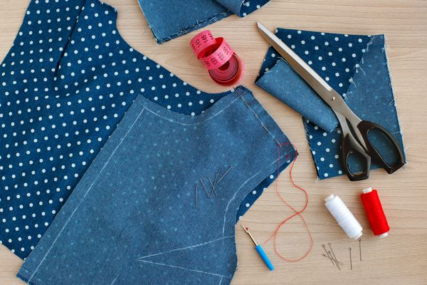 Sew clothes with needles and threads. View from above.