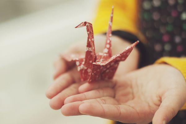 Child holding origami crane