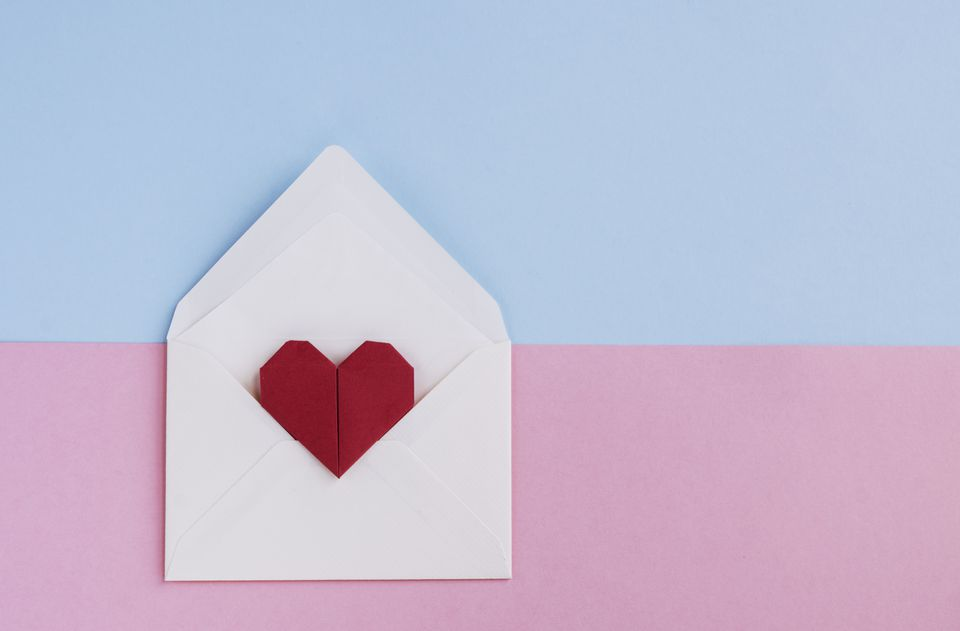 Valentine letter: Envelope with origami heart shape ready for love message on pastel colored background. Directly above and Copy space