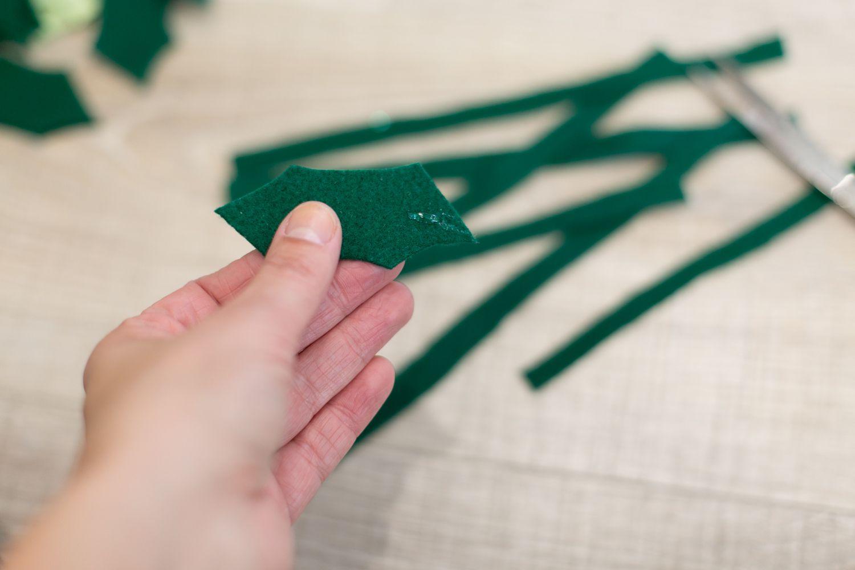 Add glue to felt holly leaves