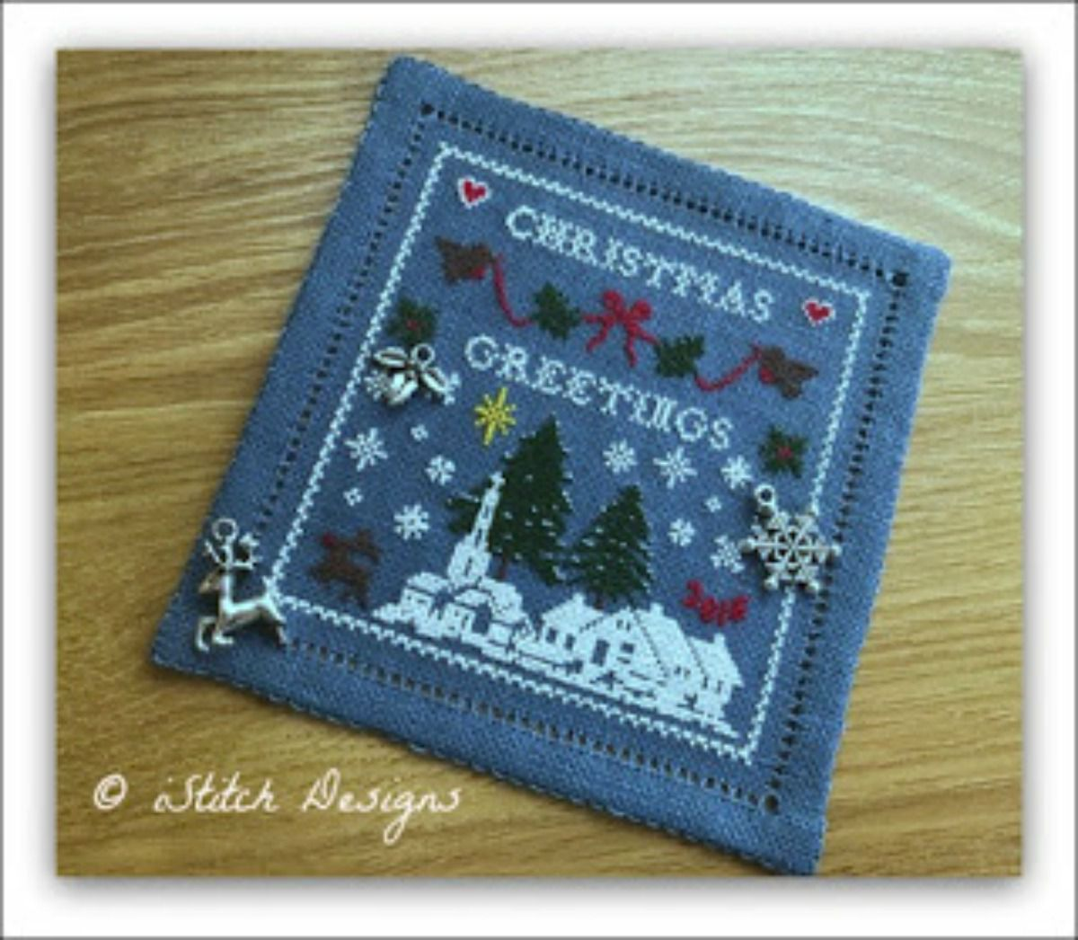 Completed blue cross-stitch design that reads Christmas Greetings.