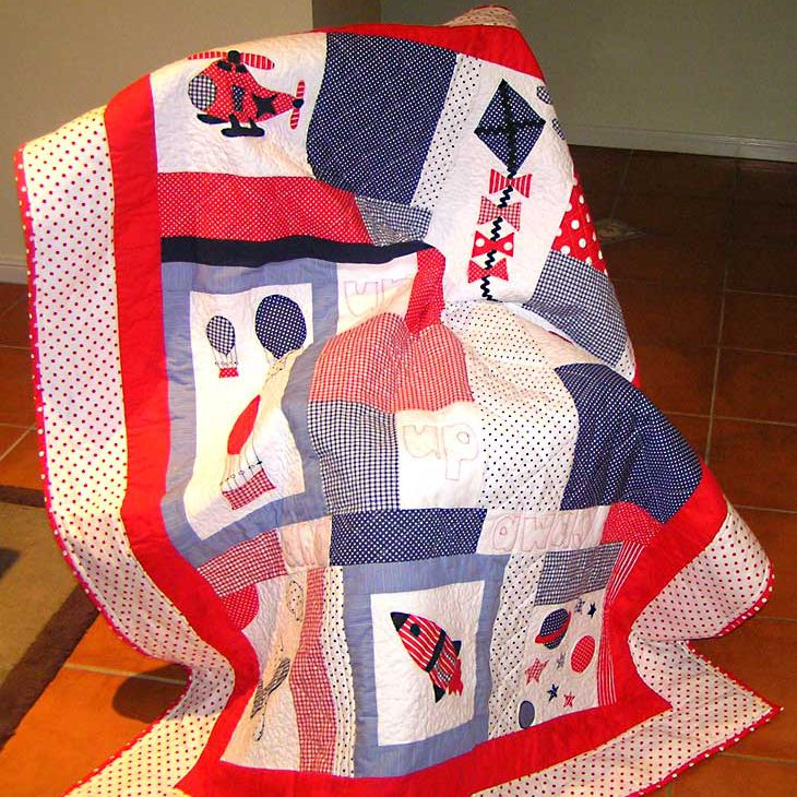 Red baby quilt with items that fly, including balloons, kites, rocket ship, and helicopter.