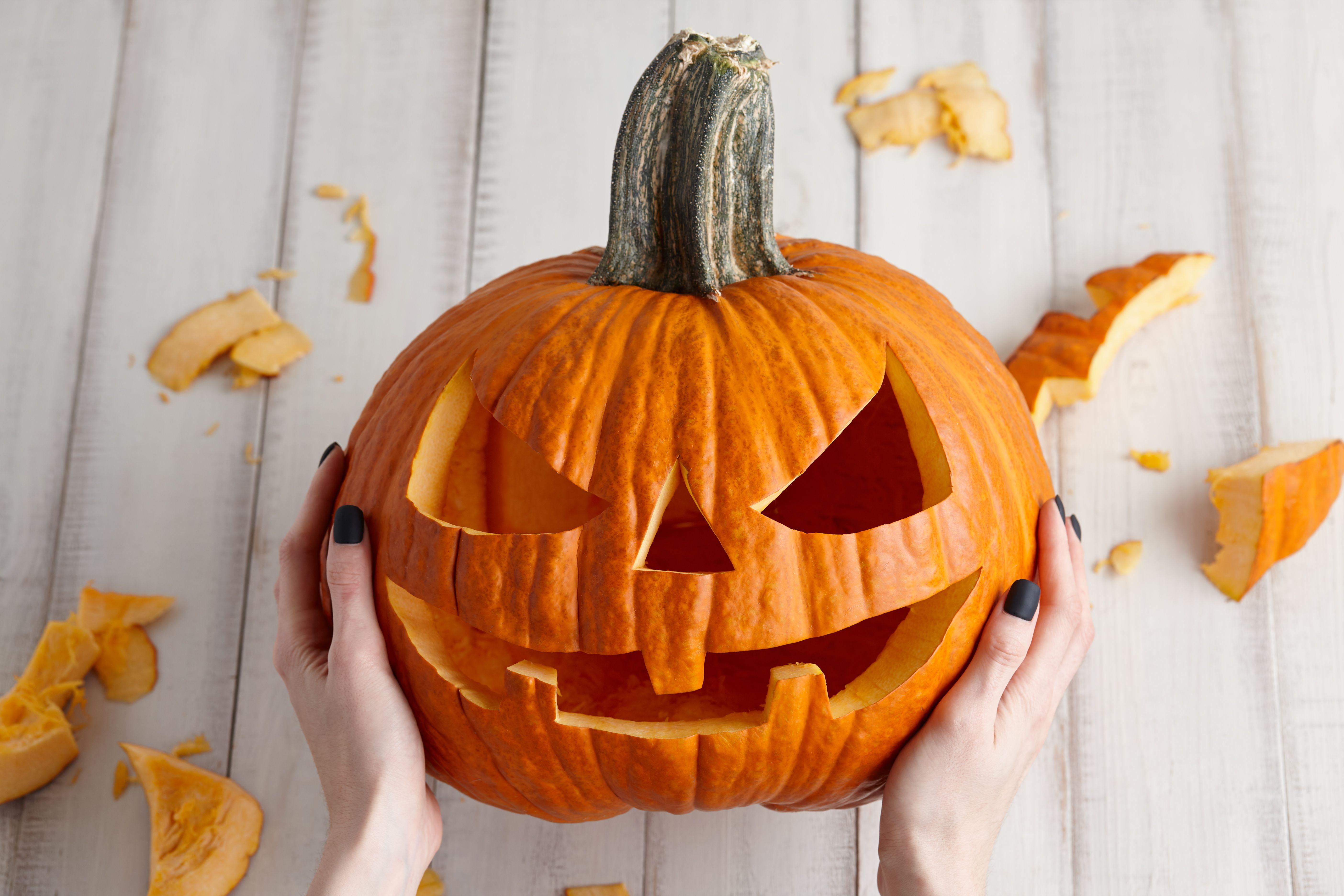 Carving halloween pumpkin into jack-o-lantern, close up view
