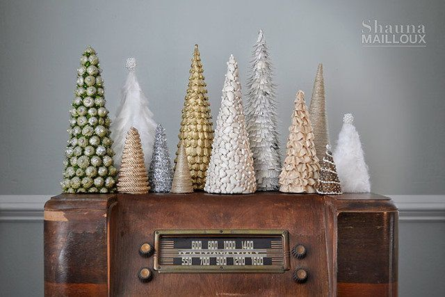 Multiple silver and gold mini Christmas trees sitting on an antique radio.