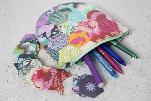 A hexagon zipper pouch filled with pens and pencils