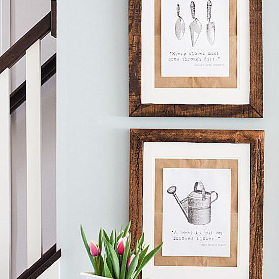 A gardening tools and water can printable art hanging on a wall.
