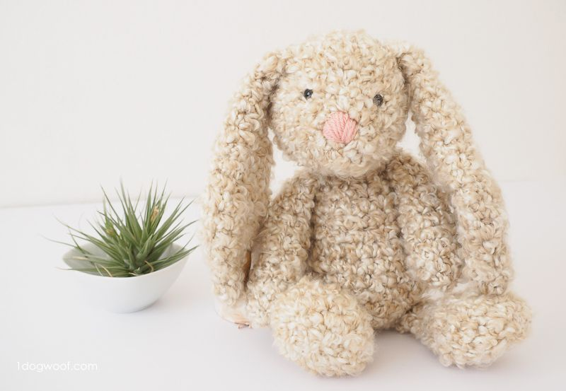 Large beige crochet stuffed bunny next to a small plant.