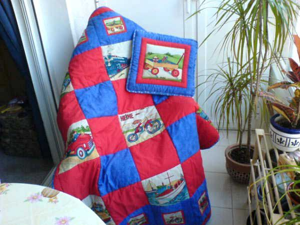 Baby quilt with red and blue squares, wagons, bicycles, boats, and cars draped over chair near a potted tree.