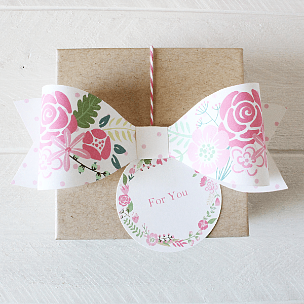 A printable pink and green paper bow on top of a gift.