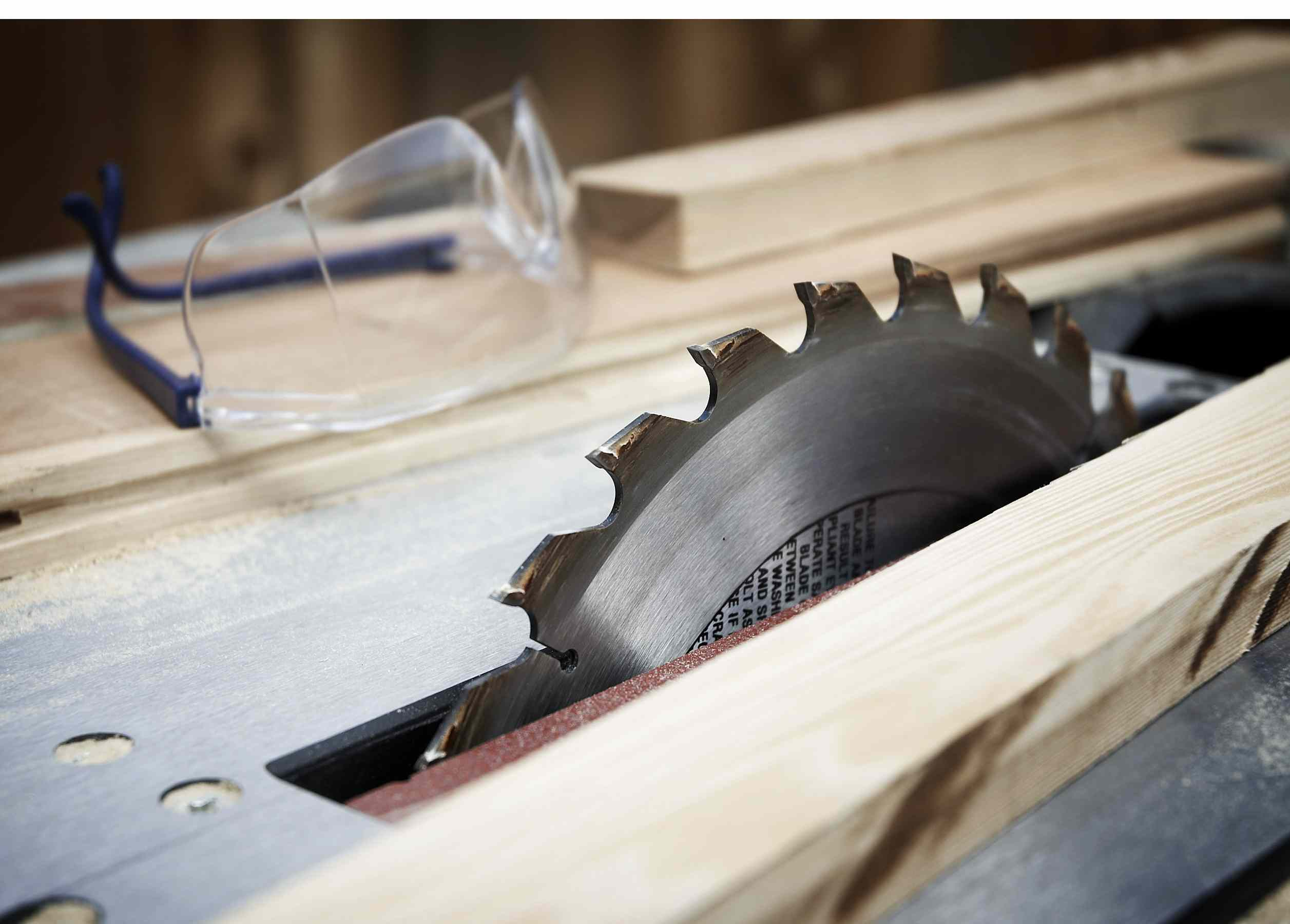 A table saw with wood and safety goggles