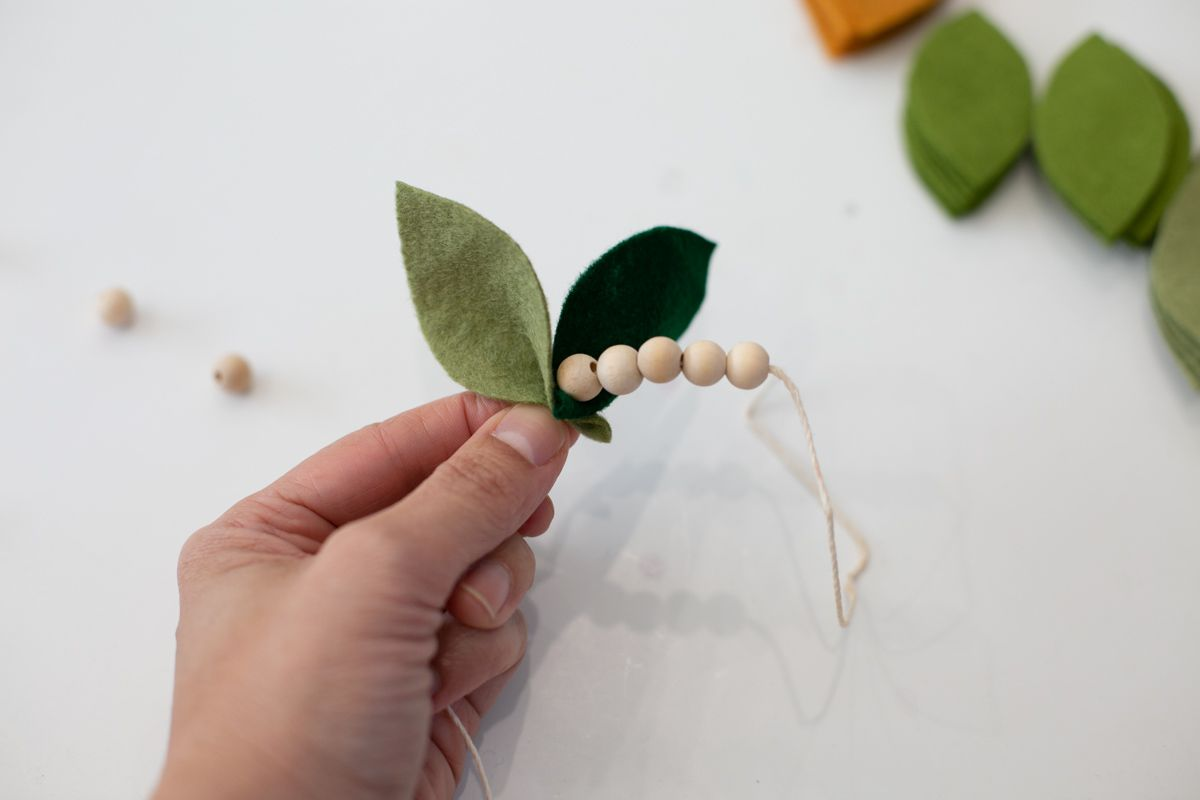 Stringing felt leaves and wooden beads on garland