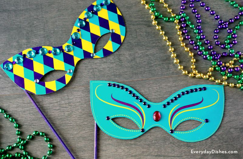 Two colorful Mardi Gras masks with beads on a table
