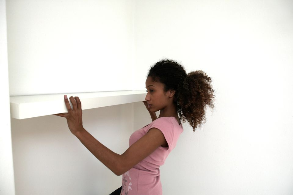 Young woman erecting shelf, side view