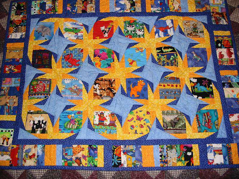Baby blanket with orange pinwheels and numerous colorful designs.