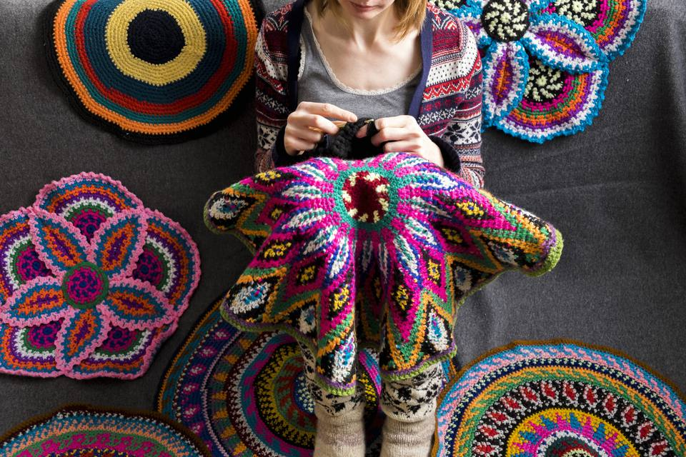 woman crocheting on the floor