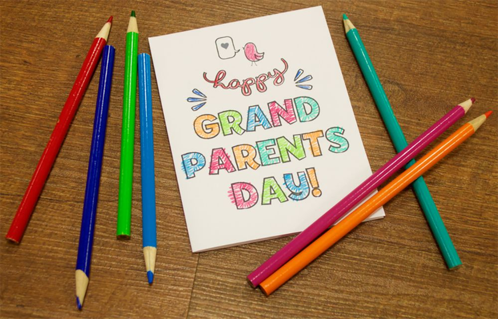 A colored grandparent's day card on a table with colored pencils