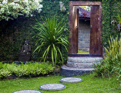 Door and Budha statue in the garden. Bali. Indonesia.