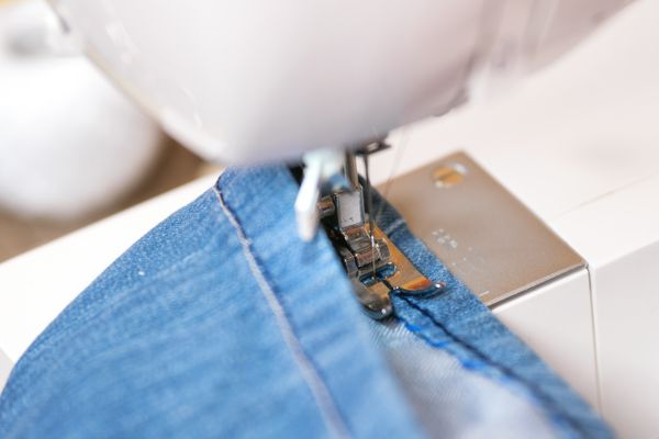 Sewing denim jeans with sewing machine. Repair jeans by sewing machine.