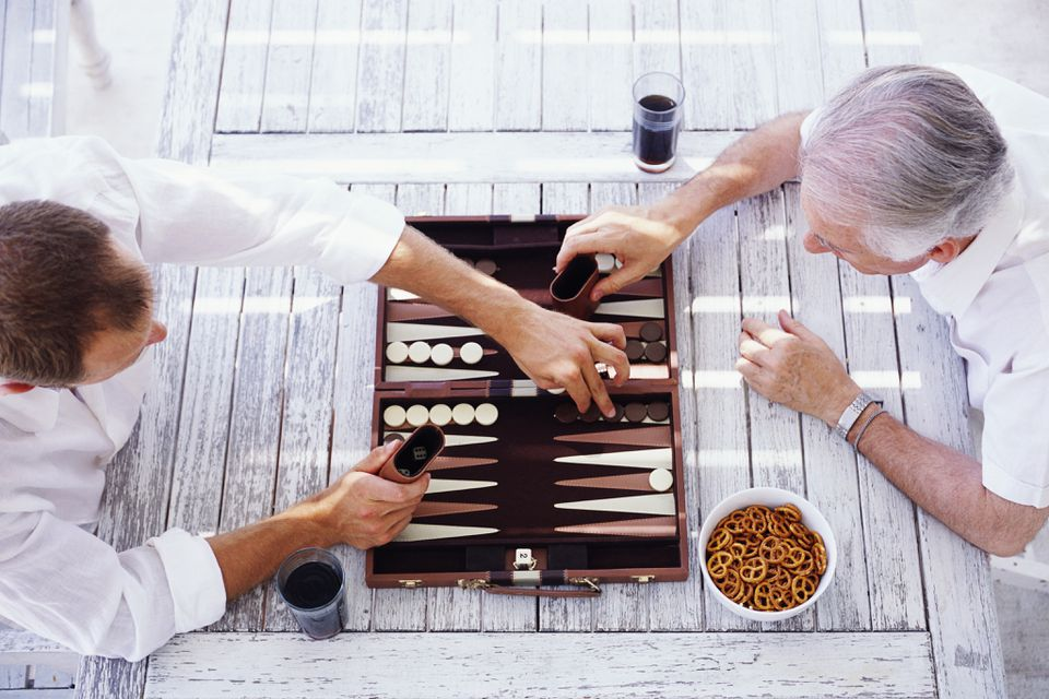 Men Playing Backgammon on Wooden Table