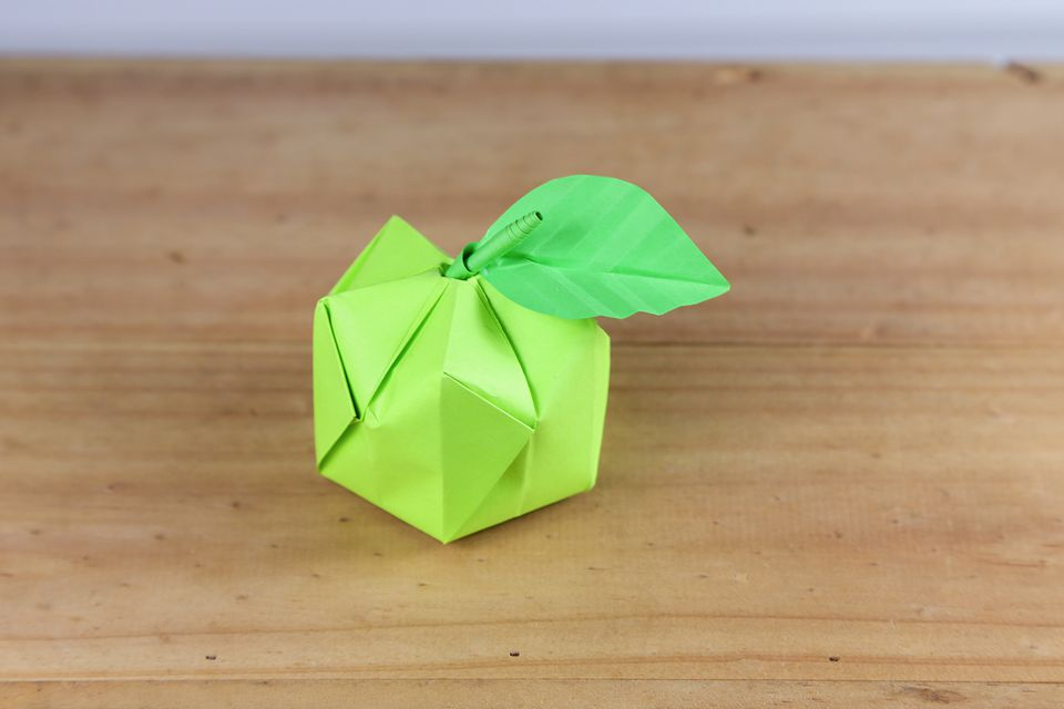 A completed yellow origami apple with leaf.