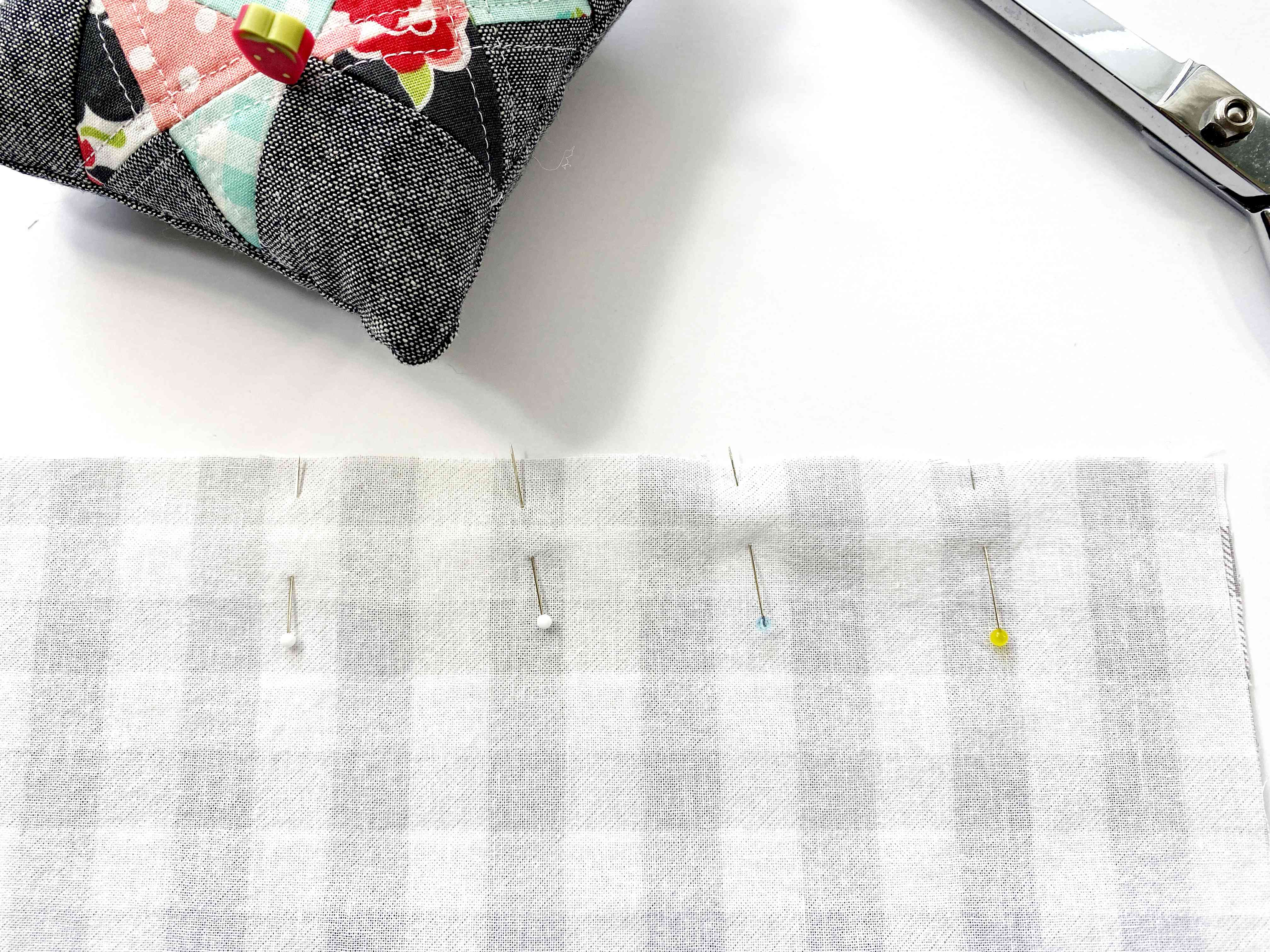 Pins in fabric, scissors, and a pincushion
