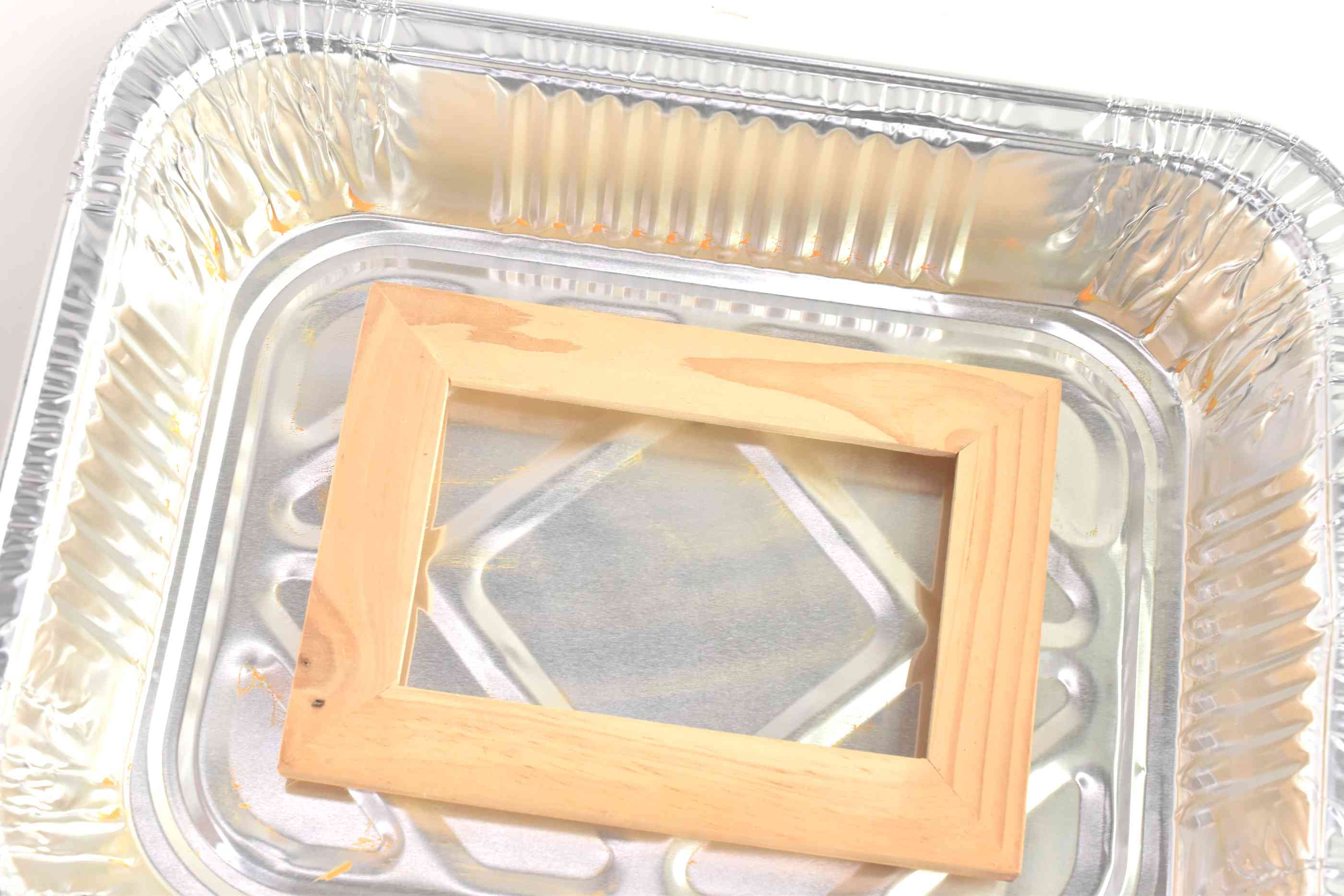 Plain wooden picture frame in a metal tray