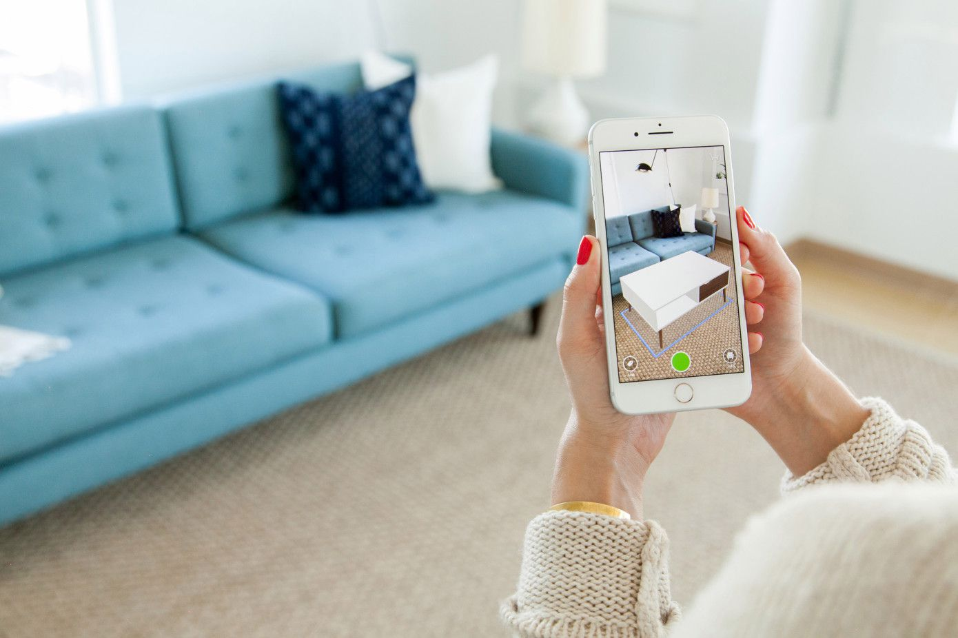 Woman's hands holding smartphone with camera aimed at living room couch.
