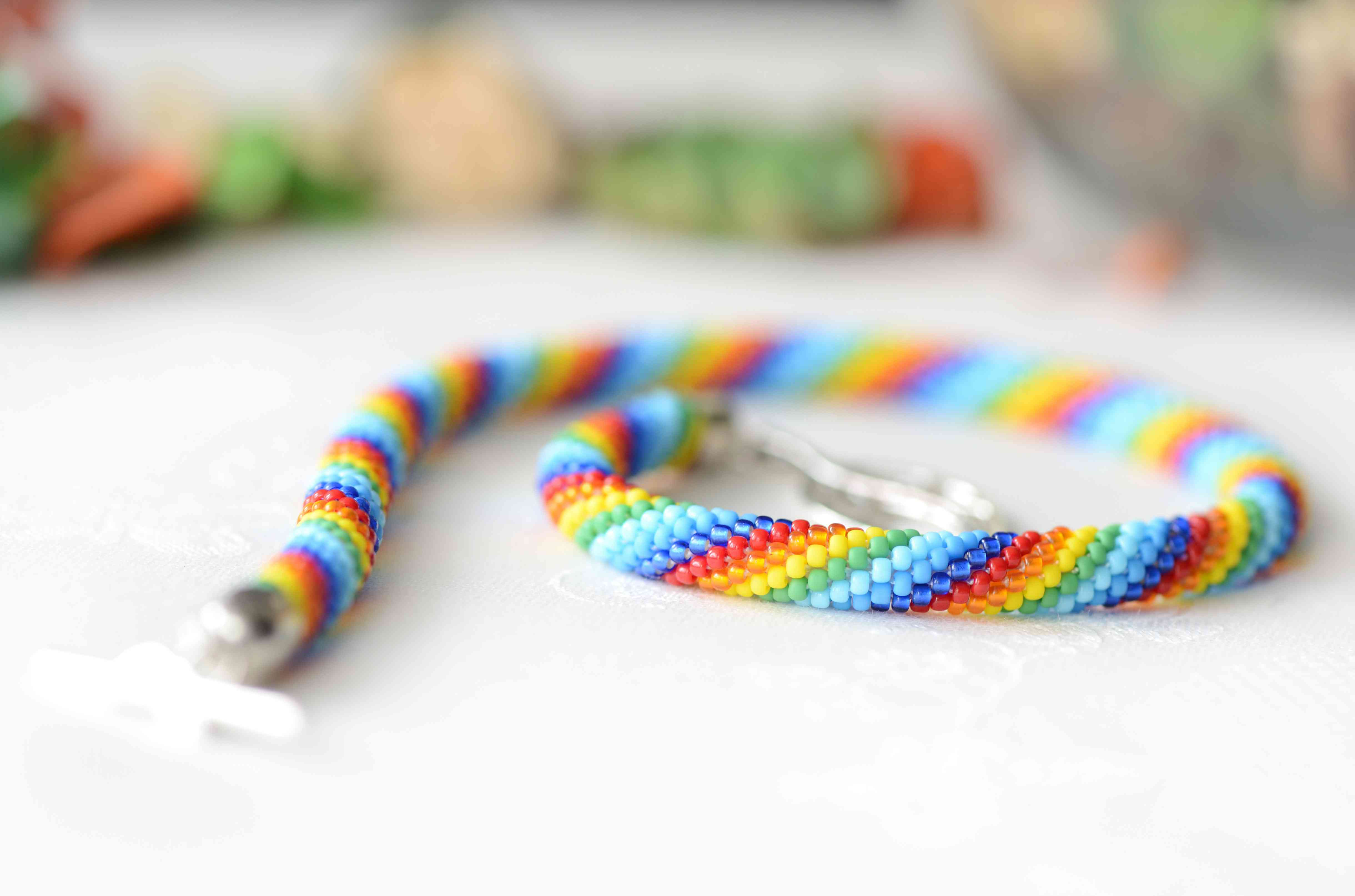 Rainbow beaded necklace on a textile background close up