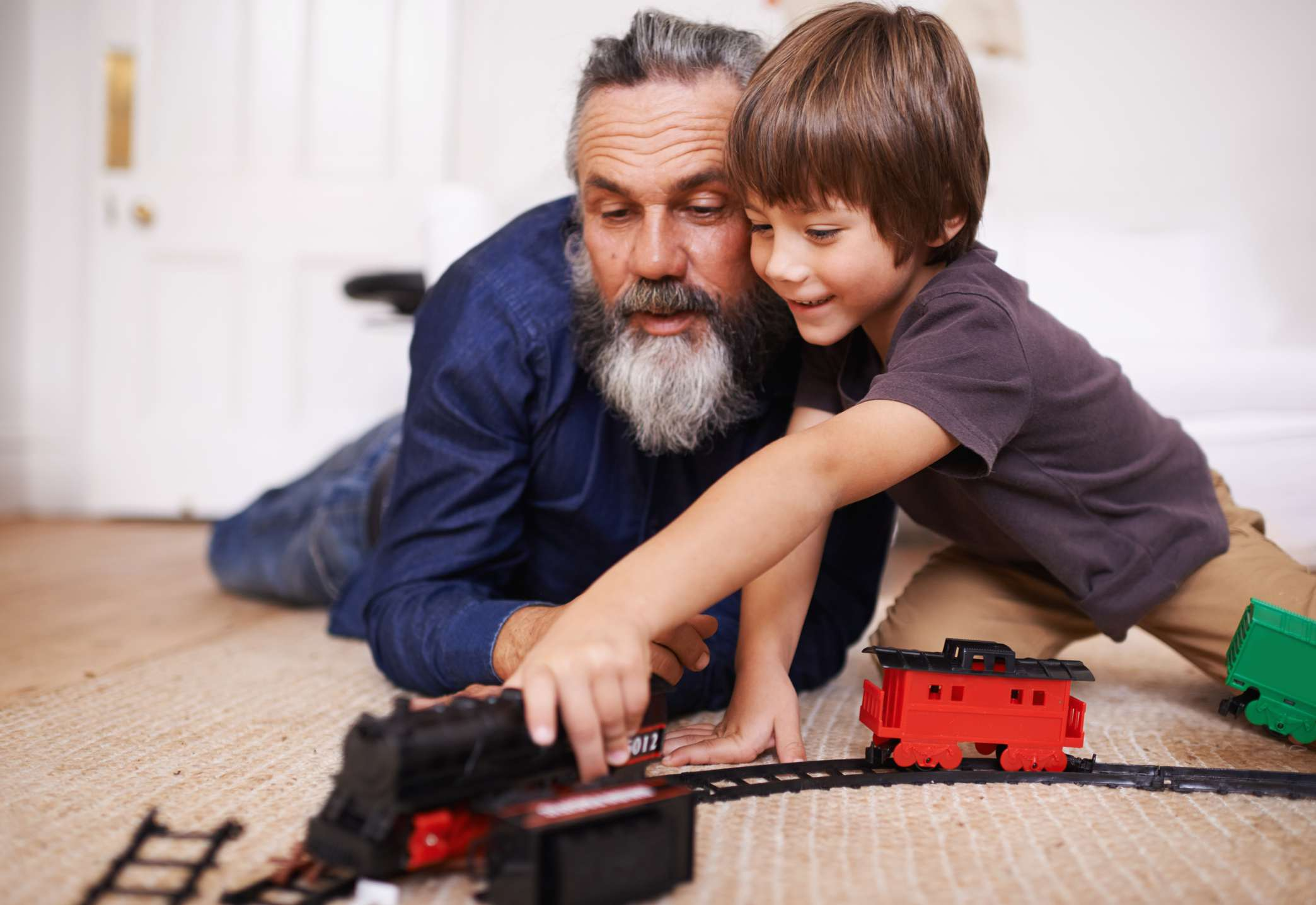 Boy showing his grandpa an electric train set.