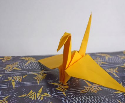 Yellow origami crane sitting on a table.