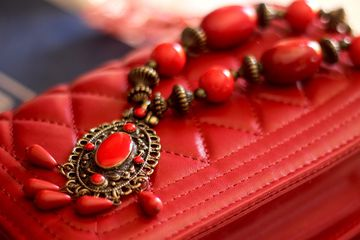 Red vintage necklace with red pendant on top of red purse.
