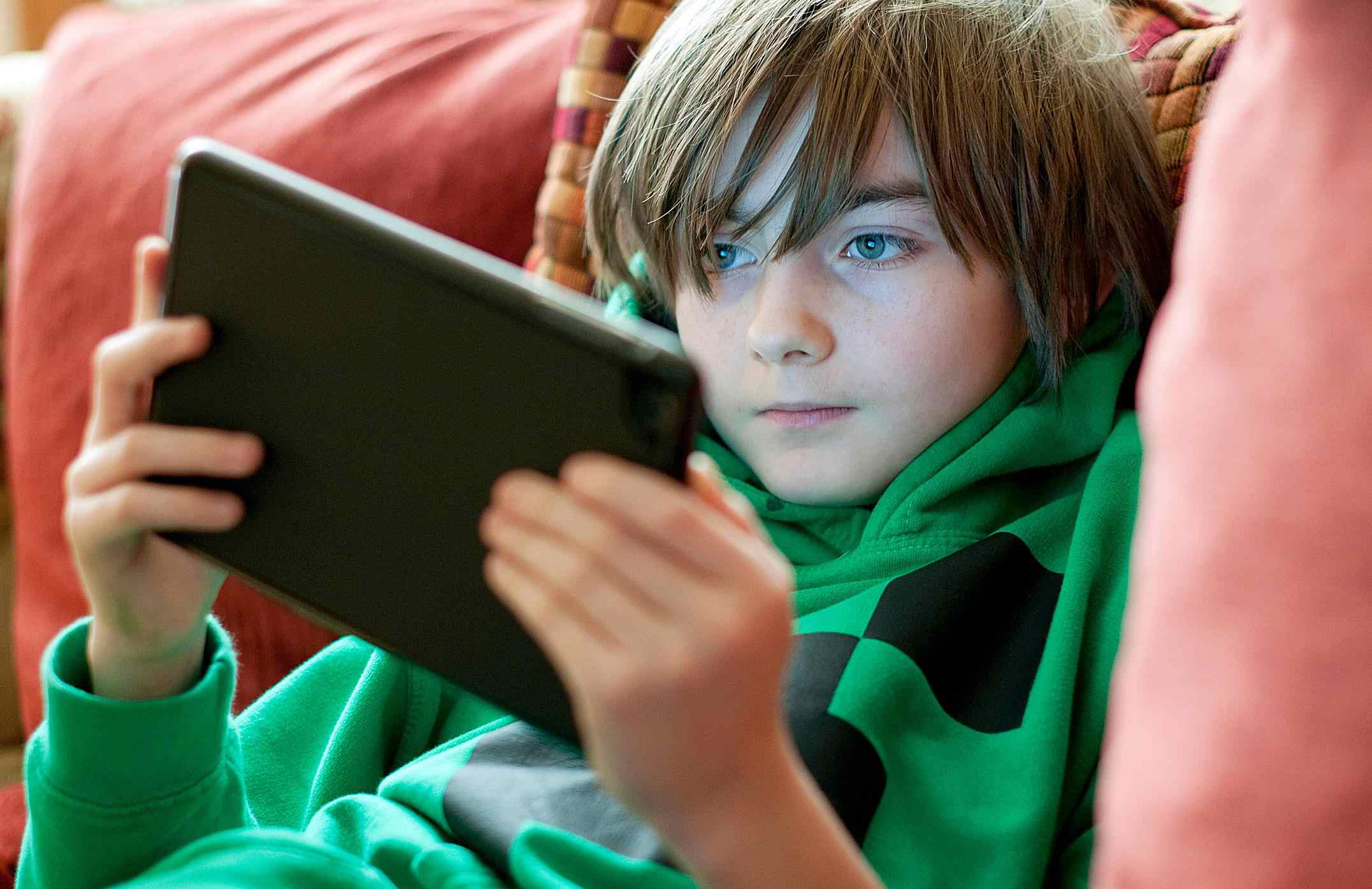 Boy playing games on digital tablet
