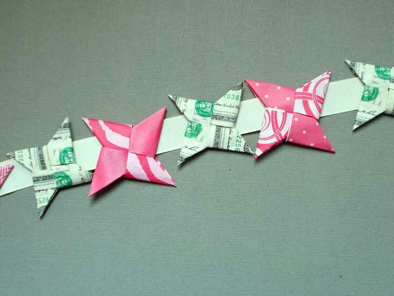 Dollar bill and origami ninja stars arranged in a row