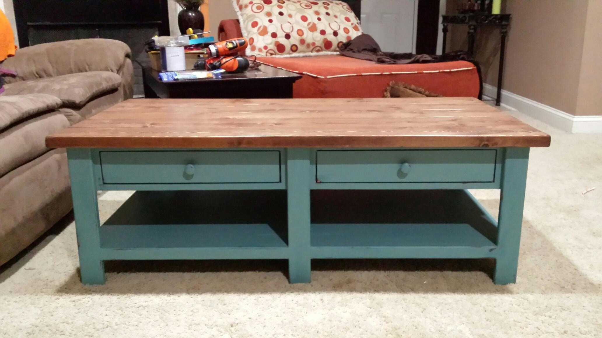 A Coffee Table With Two Drawers And Lower Bench